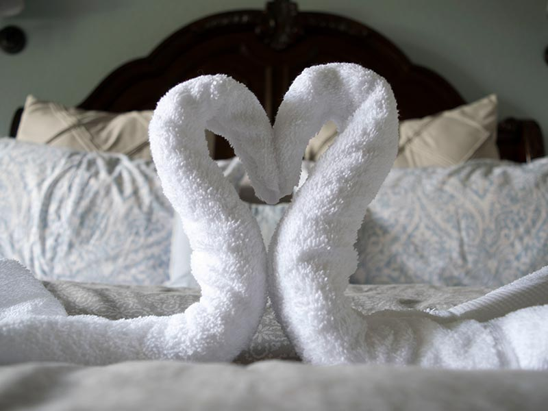 Towels in the shape of a heart on the bed of the Regency room.